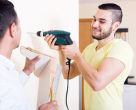 Two skilled men doing maintenance. Two cheerful men doing maintenance work at home stock photos