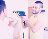 Two skilled men doing maintenance. Two cheerful men doing maintenance work at home stock images