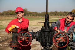 Two Skilled Oil and Gas Engineers in Action at Oil Well. Two oil and gas engineers working on oil rig equipment stock image