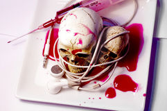 Two skulls and hypodermic. Royalty Free Stock Image