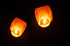 Two sky lanterns in the sky at night Stock Photos