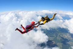 Two skydivers in color suits are falling above white clouds. stock image