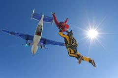 Two skydivers in color suits have just jumped out of an airplane. Skydiving. Fun jump. Girl in red suit is gripping hands of her instructor in yellow suit. They royalty free stock photos