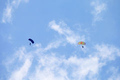 Two skydivers with colourful chutes circling in queue for landin Stock Photos