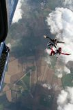 Two skydivers exit a plane. In a sit position Stock Photography