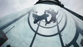 Two skydivers fly into wind tunnel. Extreme skydiving tandem in wind tunnel stock photography