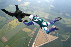 Two skydivers in freefall. Holding hands Royalty Free Stock Image