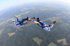 Two skydivers in striped T-shirts are flying in the sky. stock photos