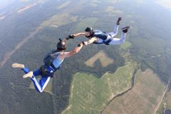 Two skydivers in striped T-shirts are flying in the sky. royalty free stock photo