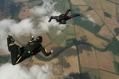 Two skydivers performaing formations. Over some clouds Royalty Free Stock Image