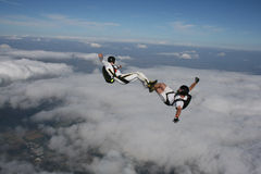 Two skydivers in a sit position while in freefall Stock Image