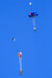Two Skydiving Base Jumpers Falling Fast. Two base jumpers each with a very colorful parachutes starting to deploy fall fast after leaping from the New River Royalty Free Stock Photography