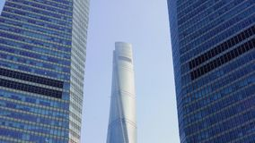 Two skyscrapers between which the third one is visible against the blue sky in the Pudong area, Shanghai, China.  stock video footage