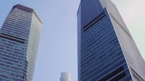 Two skyscrapers between which the third one is visible against the blue sky in the Pudong area, Shanghai, China.  stock footage