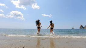 Two slender brunettes with long hair in black bikinis running into the sea. In slow motion stock video footage