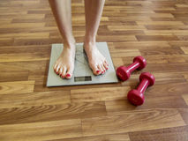Two slender female legs stand on electronic scales. And two red dumbbells on the floor near the scales hint that the girl needs to watch the weight Royalty Free Stock Photography