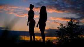 Two slender girl resting after jogging and watching the sunset. Shot at Sony camera in 4K stock footage