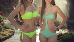 Two slender girls in bikini under the splashes of. Two slender girls in bikini under splashes of water in the garden stock video footage