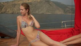 Two slender models in bathing suits sitting on the deck of yacht stock video