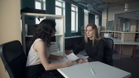 Two slender women sit at the table in the office and talk. A brunette in a white blouse listens with documents at her desk, a blonde in a black suit. Employees stock video