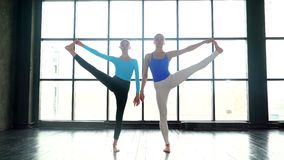 Two slender yoga women practicing extended triangle pose in the studio with natural light. Young womans doing yoga. Two slender yoga women practicing extended stock video
