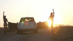 Two slender young women got out of the car and hold up their hands to reach the last sunset sunshine