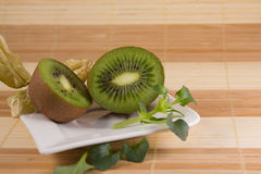 Two sliced kiwis on a white plate. With bamboo background Royalty Free Stock Photo