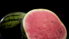 Two sliced water-melons. UHD Two gigant huge big green striped wet fresh tasty sliced water-melons with red juicy ripe on black surface and bg 4k. Glidetrack stock video footage