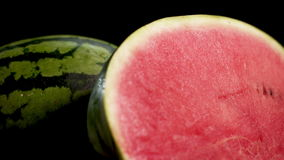 Two sliced water melons. Ultra HD Two gigant big green striped wet fresh tasty half sliced water melon with red juicy ripe on black surface and background 4k stock footage