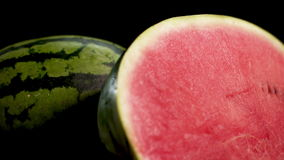 Two sliced watermelons. UltraHD Two gigant huge big green striped wet fresh tasty half sliced watermelon with red juicy ripe on black surface and background 4k stock video footage