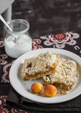 Two slices of apricot pie on a white plate and natural yogurt in a glass jar on brown fabric Stock Image