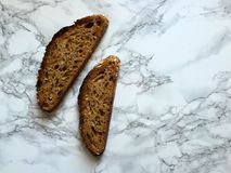 Two slices of artisanal sourdough whole wheat bread on marble countertop Royalty Free Stock Photo