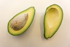 Two slices of avocado isolated on the white background. One slice with core. Design element for product label. Two slices of avocado isolated on the white Stock Photo