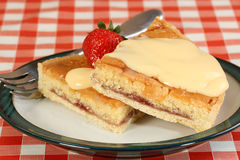 Two slices of bakewell tart with custard Stock Photography