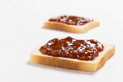 Two slices of bread with apricot jam on white  table Royalty Free Stock Photography