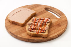 Two slices of bread coated with pate and ketchup on wooden board.  Stock Photography