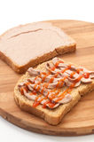 Two slices of bread coated with pate and ketchup on wooden board.  Stock Images