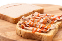 Two slices of bread coated with pate and ketchup on wooden board Stock Photos