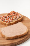 Two slices of bread coated with pate and ketchup on wooden board Stock Image