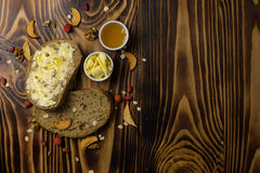 Two slices of bread and a cup of honey and butter, peanuts and decorated with pieces of dried apple lying on a wooden backgroundt. Two slices of bread and a cup Stock Images