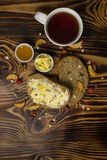 Two slices of bread, cup of tea and a cup of honey and butter, peanuts and decorated with pieces of dried apple lying on a wooden. Background. Top of view Stock Photo