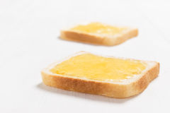Two slices of bread with honey on white wooden table Stock Photo