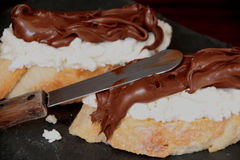 Two slices of bread, ricotta cheese and spreadable cream of cacao and hazelnuts. Two slices of bread, ricotta cheese and a spresdable sweet cream of cacao, milk Stock Photos