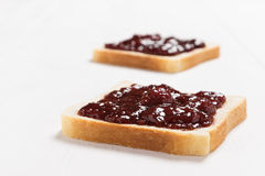 Two slices of bread with strawberry jam on white table Royalty Free Stock Image