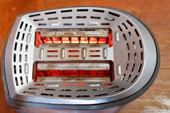 Two slices of bread toasting in metal toaster Royalty Free Stock Photography