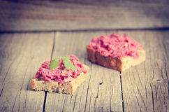 Two slices of bread on a wooden table with beetroot spread. Natural background and healthy, vegetarian and vegan food. Fast breakf Royalty Free Stock Photography