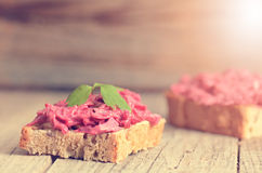 Two slices of bread on a wooden table with beetroot spread. Natural background and healthy, vegetarian and vegan food. Fast breakf Royalty Free Stock Image