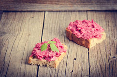 Two slices of bread on a wooden table with beetroot spread. Natural background and healthy, vegetarian and vegan food. Fast breakf Royalty Free Stock Photos