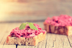 Two slices of bread on a wooden table with beetroot spread. Natural background and healthy, vegetarian and vegan food. Fast breakf Stock Photo