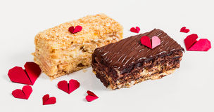 Two slices of cake napoleon with chocolate and red paper hearts Royalty Free Stock Photo